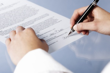 Macro of businesswoman signing contract.